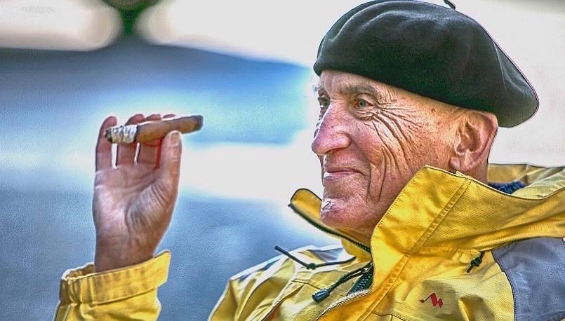 Älterer Mann, der eine Zigarre und ein Lächeln genießt